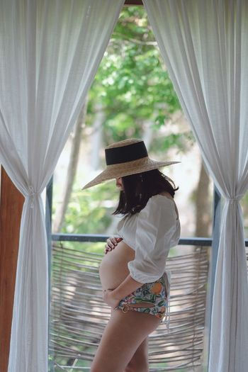 Curtain One Person Window Women Clothing Hat Standing Human Arm Three Quarter Length Holding Young Women Young Adult Rear View Leisure Activity Day Adult Lifestyles Real People Indoors  Sun Hat