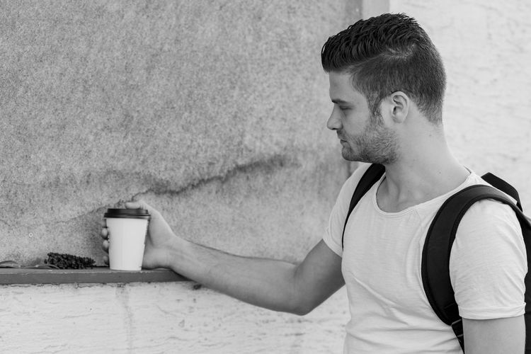 Midsection of man holding drink against wall