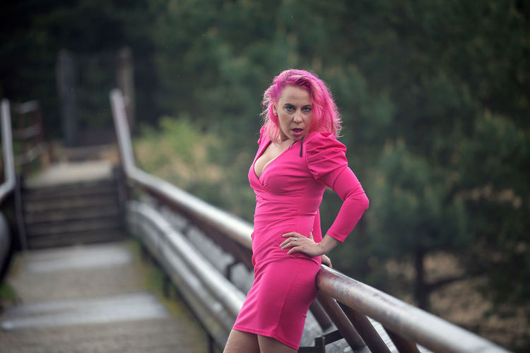 Portrait of young woman standing on pink railing