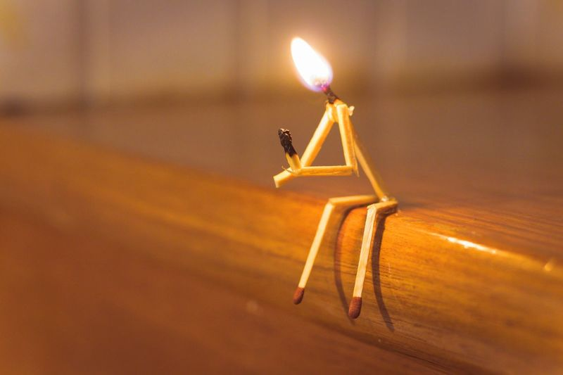 Close-up of person made from matchsticks burning on wooden table