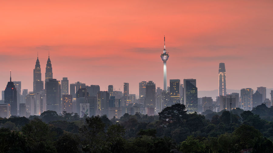 The city of Kuala Lumpur, Malaysia during Sunrise Kuala Lumpur Malaysia Klcc Kl Twin Tower Towers Sky Orange Sky Tree Sunrise Sunset Golden Hour Clouds Skyscraper City Cityscape Panorama Panoramic Sun Rays Light Shadow Silhouette Building Architecture Forest Flare