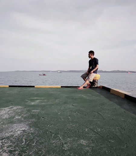 Young man on sea against sky