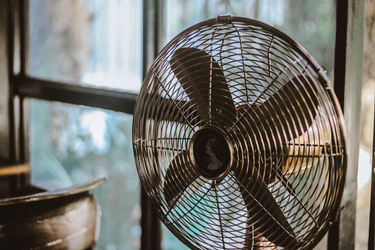 Close-up of vintage electric fan by window at home