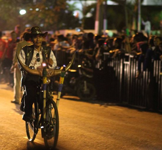 Man wearing cowboy hat riding bicycle on street at dusk during event