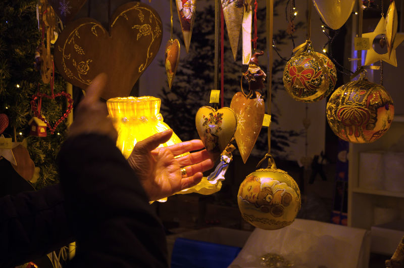 Midsection of man holding decoration at market stall