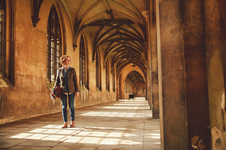 Woman Standing In Corridor Of Church