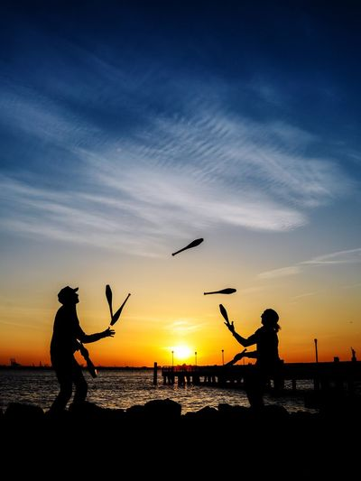 Silhouette Friends Juggling Bottles At Beach Against Sky During Sunset