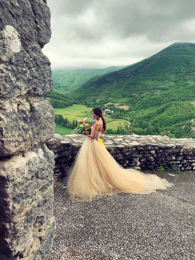 Woman holding bouquet while standing on mountain against sky