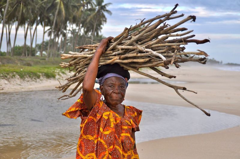 Portrait of senior woman with stack of logs on head at beach