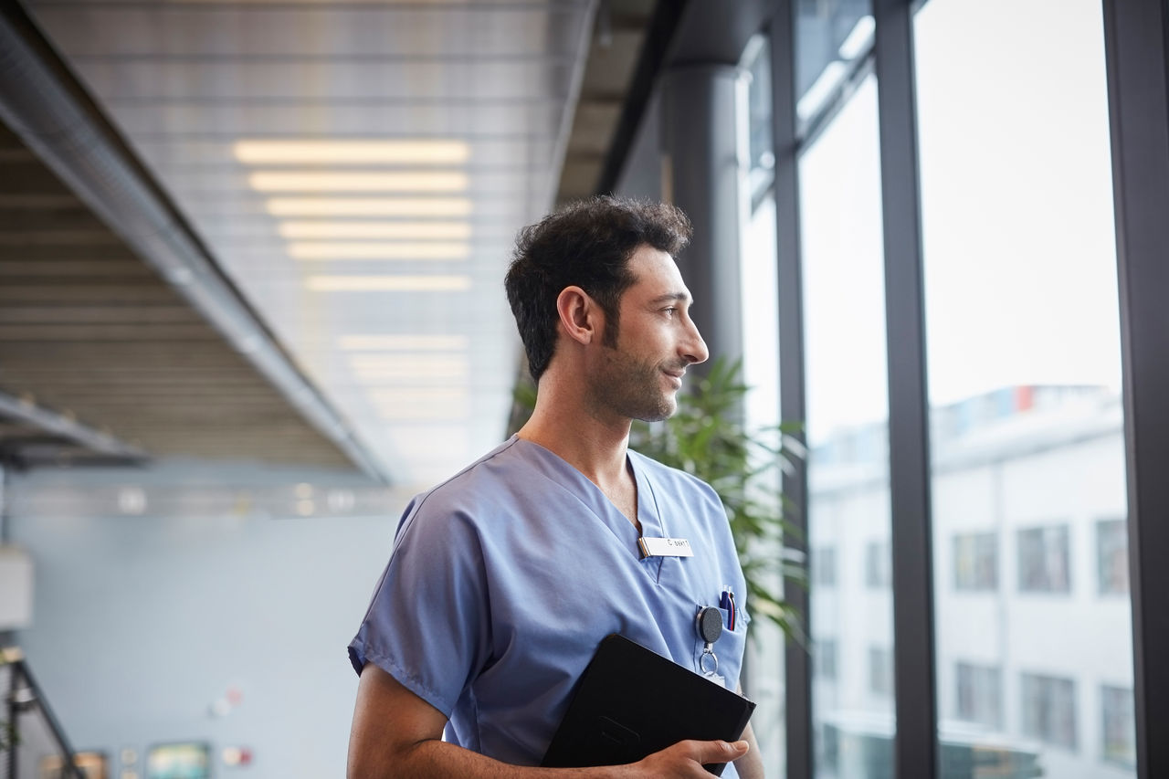 Thoughtful Young Male Nurse Holding Digital Tablet While Looking Through Window At Hospital