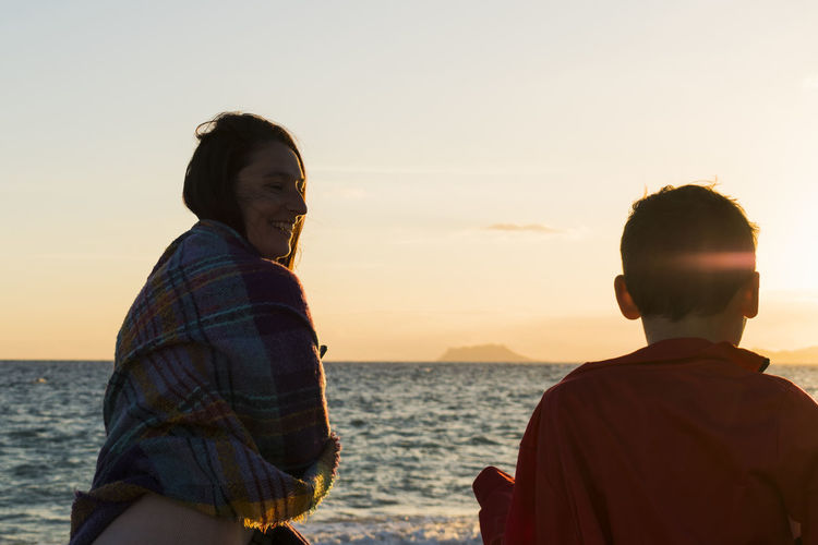 Mother and son at beach against sea and sky during sunset
