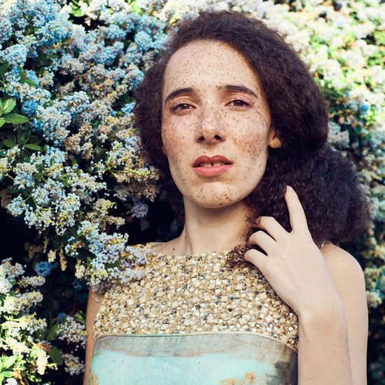 Portrait Of Woman With Freckles On Face Against Plants