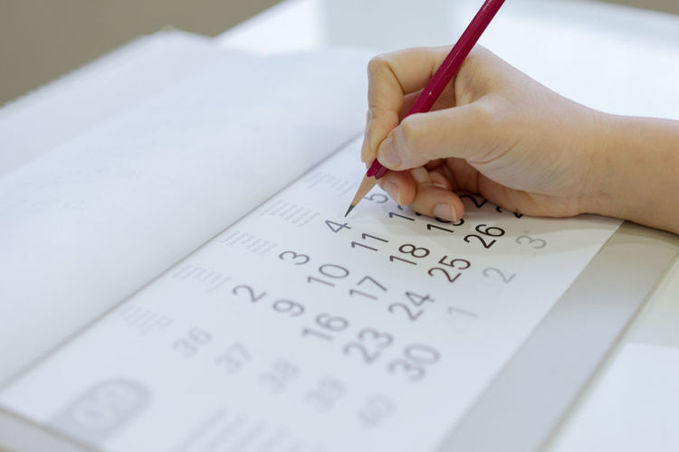 Cropped hand of person writing in calendar with pencil