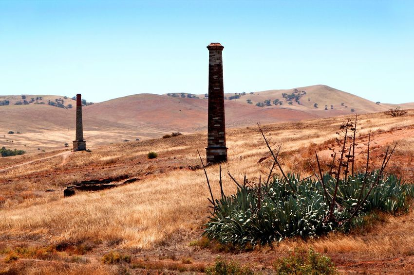 Chimney stacks in an abandoned Copper Mine, Burra, South Australia Copper Mine Travel Photography Abandoned Mine Arid Climate Arid Landscape Beauty In Nature Blue Burra Chimney Stacks Clear Sky Day Desert Grass Growth Landscape Mountain Nature No People Outdoors Plant Scenics Sky Tranquil Scene Tranquility