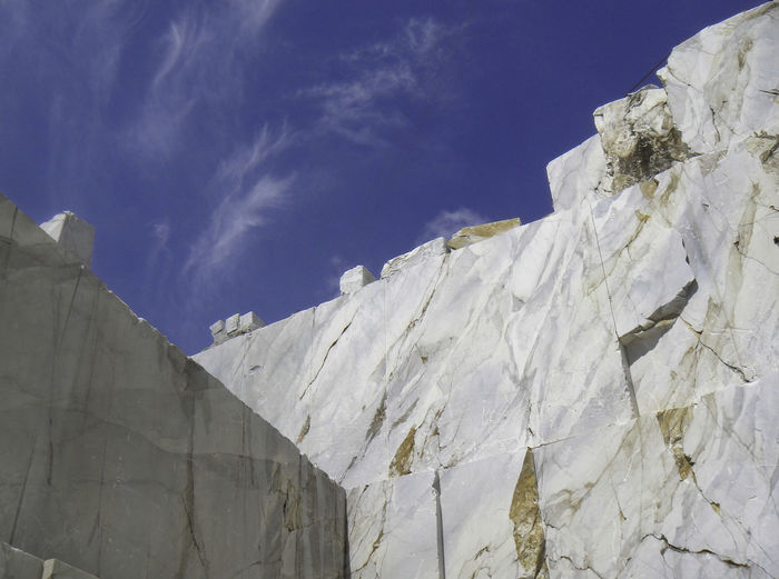 Low angle view of snow covered rocks against blue sky