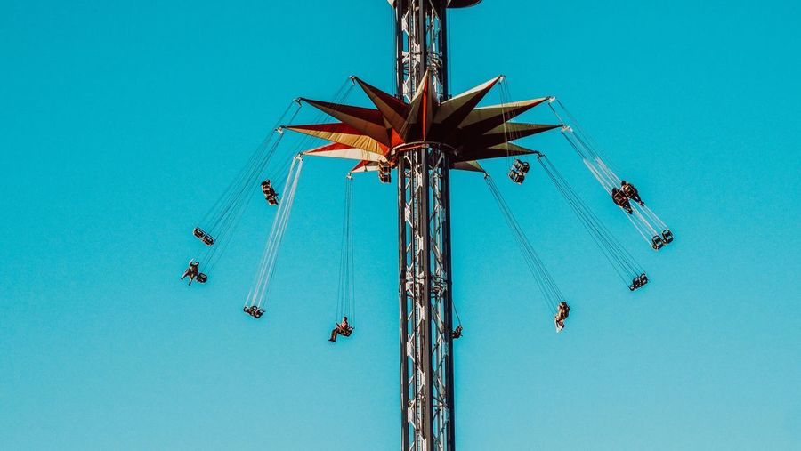 Low angle view of people enjoying chain swing ride against clear blue sky