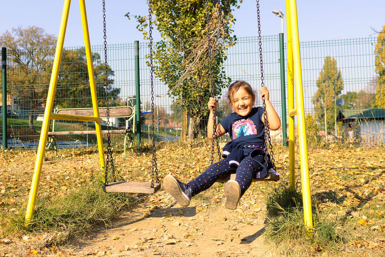 Full length of girl on slide at playground