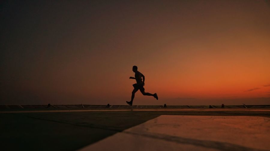 Silhouette man jumping against clear sky during sunset