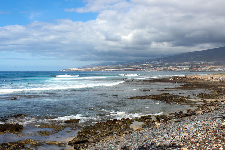 Stony beach at playa de las americas on canary island tenerife with blue water