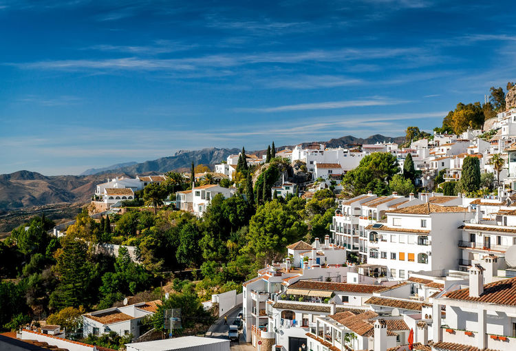 High angle view of white village of mijas amidst trees against sky