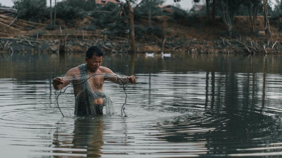 Full length of shirtless man holding water in lake