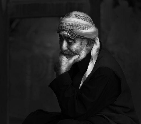 Thoughtful Senior Man Wearing Headscarf