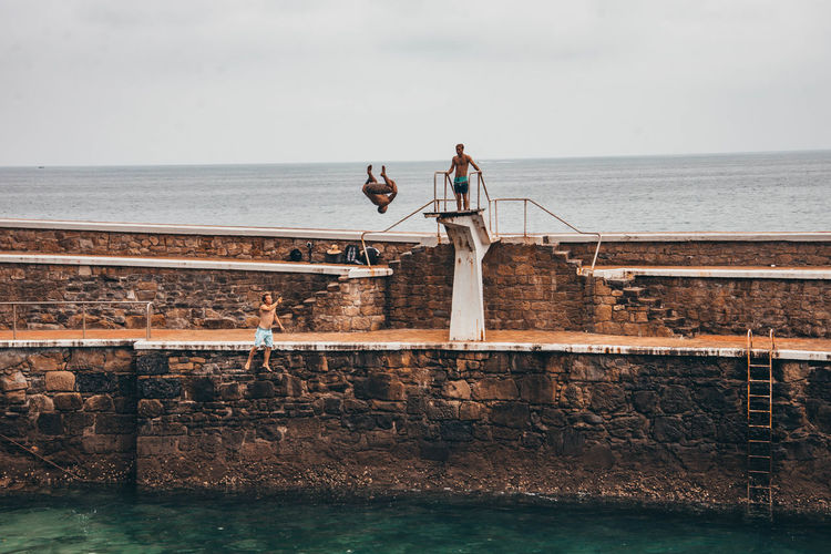 People standing by railing against sea