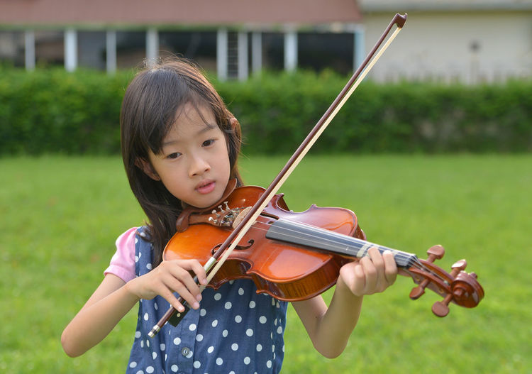 Girl Playing Violin On Grassy Field At Public Park