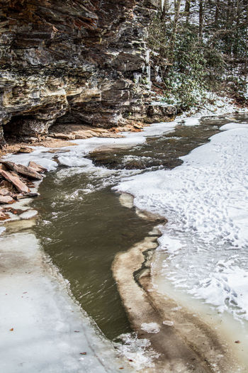 View of stream flowing in winter