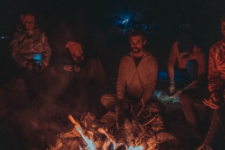 Group of people against fire at night