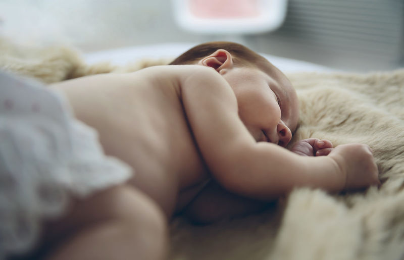 Cute baby girl sleeping on bed