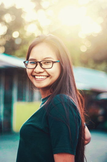 Eyeglasses  Smiling Portrait Young Adult Happiness Teenager Looking At Camera People Cheerful Young Women Beautiful People Casual Clothing Human Face Sunshine Sunbeam Sunlight Sun Outdoors Long Hair