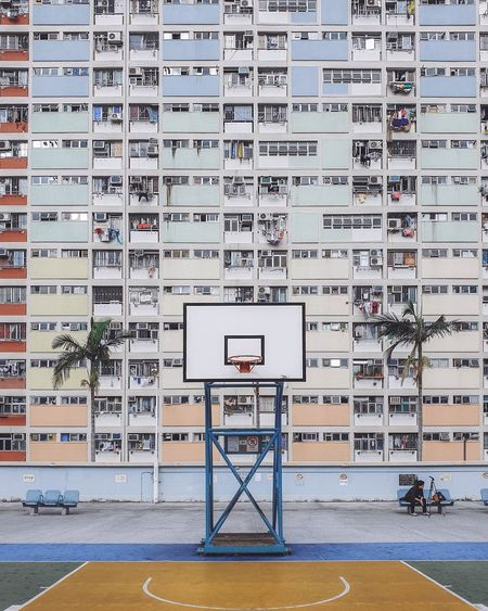 Low angle view of basketball hoop against buildings in city