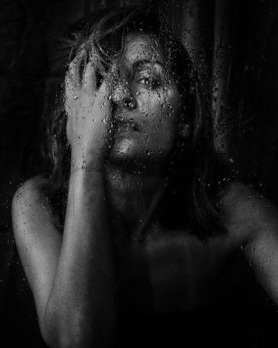 Close-up portrait of woman seen through wet window against black background