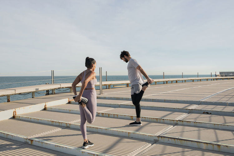 Side view of couple standing on railing by sea against sky
