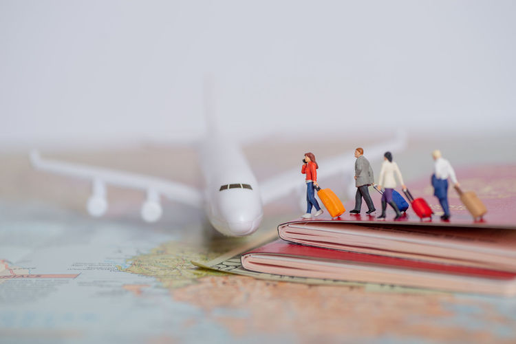Miniature passenger concept of people travel to foreign land - insurance or medical tourism concept. Holiday Map Mobile Phone Passenger Passport Tourist Travel Vacations Woman Airplane Baggage Communication Concept Departure Group Insurance Luggage Protection Studio Shot Talking Terminal Traveler Us Currency Voyage Women