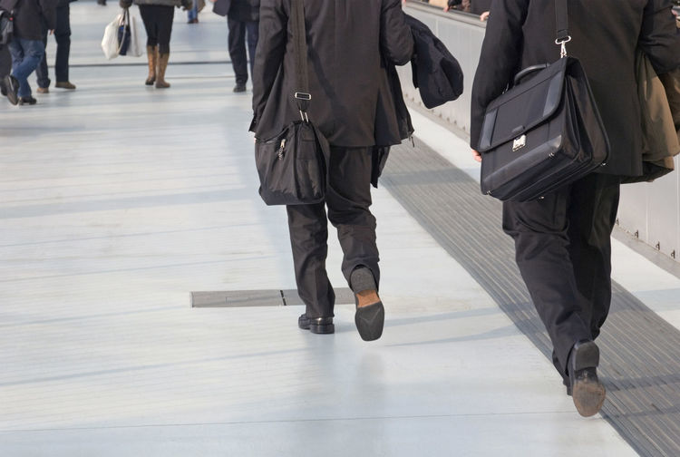 Low section of people walking on floor in city