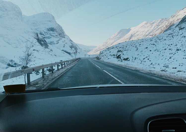 Road amidst snowcapped mountains seen through car windshield