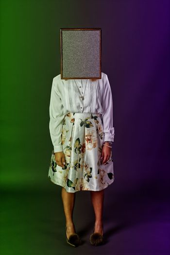 Woman with box on head against colored background