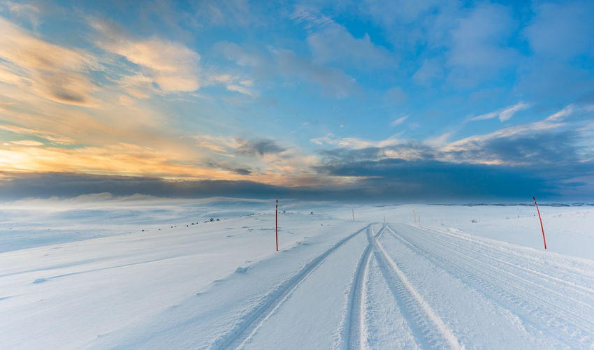 Ice Road with tire tracks on snow in Arctic landscape with the blue sky starting to turn gold as the sunset approaches. Tire Tracks Adventure Arctic Ice Road Road Trip Scenics - Nature Sky Winter Cold Temperature Snow Cloud - Sky Beauty In Nature Transportation Environment White Color Nature Road Direction Landscape Outdoors No People The Way Forward