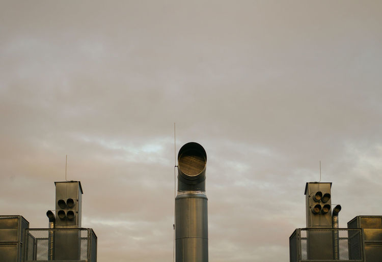 Low Angle View Of Air Duct Pipes Against Sky In Industry
