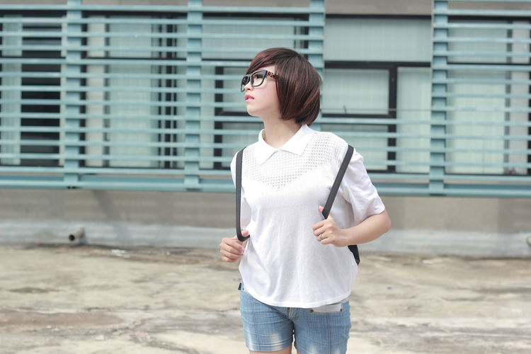 Standing Casual Clothing One Person Three Quarter Length Architecture Built Structure Day Front View Real People Building Exterior Young Adult Leisure Activity Looking Glasses Lifestyles Focus On Foreground Child Looking Away Fashion Outdoors Jeans Hairstyle Bangs Contemplation Teenager EyeEmNewHere