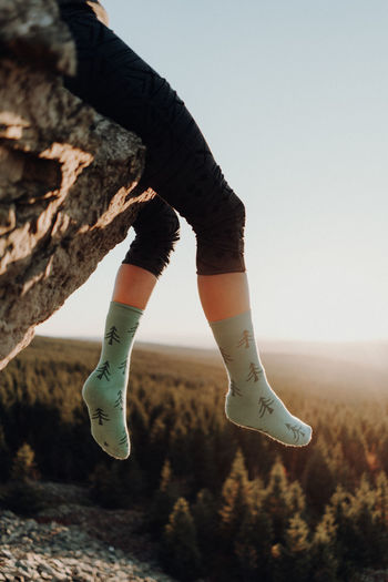 Feet in socks hanging from cliff during suset Sky One Person Lifestyles Nature Day Human Leg Low Section Real People Body Part Human Body Part Clear Sky Land Leisure Activity Casual Clothing Shoe Standing Focus On Foreground Outdoors Plant Jeans Human Limb Feet Socks Forest Sunset