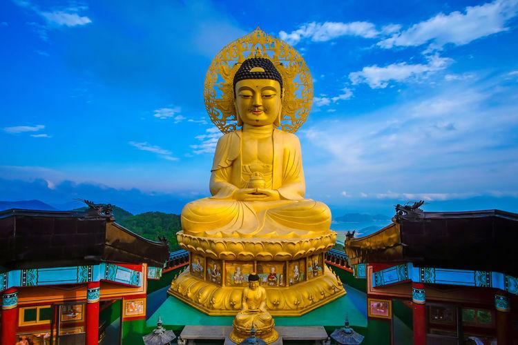 Statue against temple building against sky