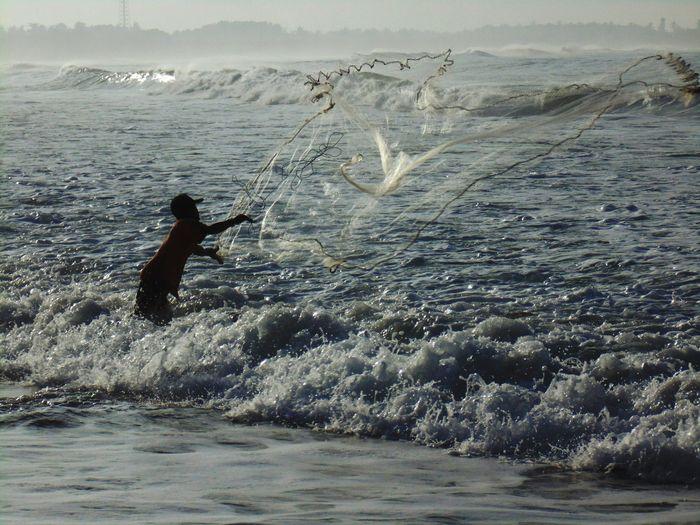 Silhouette fisherman fishing in sea