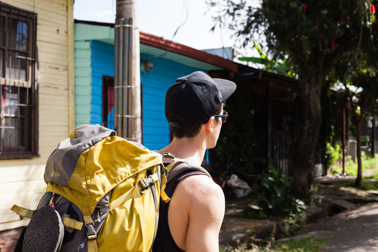 One Person Real People Architecture Day Men Building Exterior Focus On Foreground Yellow Built Structure Headshot Lifestyles Mid Adult Mid Adult Men Outdoors Nature Leisure Activity Portrait Cap Tree Backpack Backpacking Travel Destinations Travel Traveling Walking