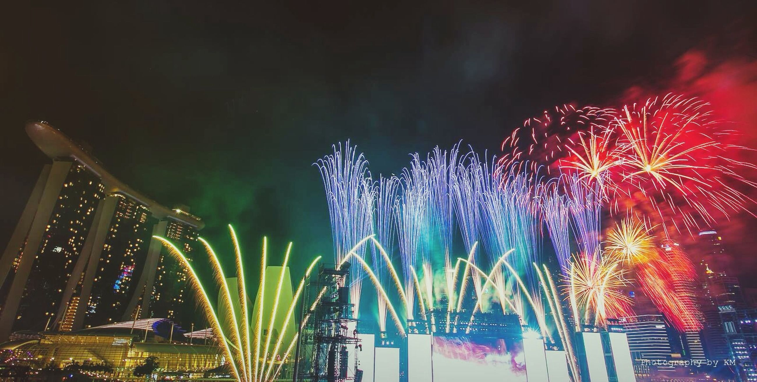 illuminated, night, celebration, firework display, long exposure, multi colored, exploding, arts culture and entertainment, firework - man made object, building exterior, motion, sky, built structure, low angle view, event, architecture, blurred motion, firework, city, celebration event