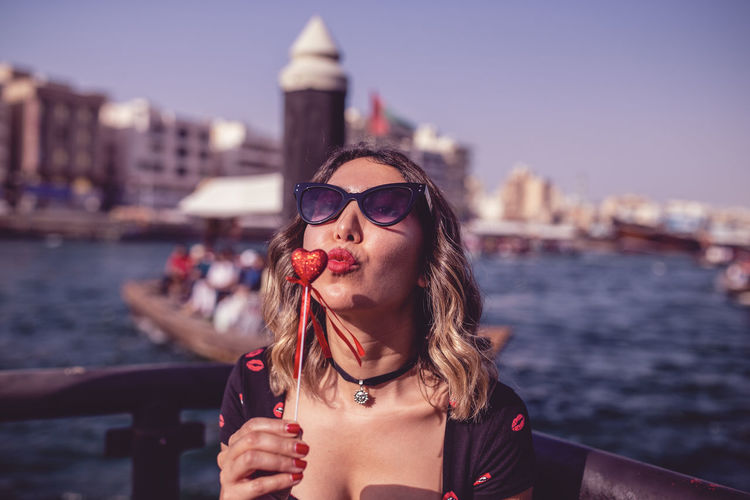 Close-Up Of Young Woman Puckering While Holding Heart Shaped Object Against Lake
