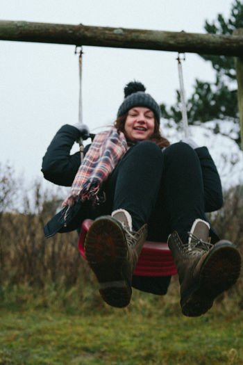 Smiling woman swinging over field against sky