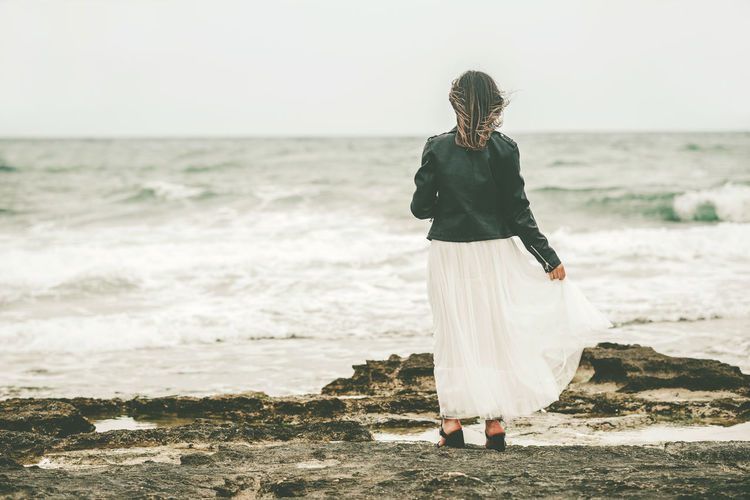 Woman standing on beach against sea